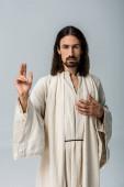 Fényképek jóképű férfi Jézus köntös kézzel a mellkason a gesztusokkal elszigetelt szürke