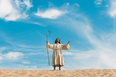 Jesus with outstretched hands holding wooden cane against blue sky in desert stock vector