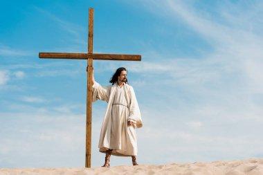Handsome bearded man standing with wooden cross in desert stock vector