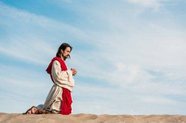 İsa mavi gökyüzüne karşı çölde sıkıştırılmış elleri ile dizler üzerinde dua