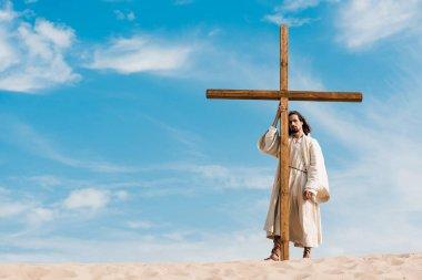 Bearded man standing near wooden cross in desert on golden sand stock vector