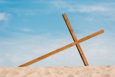 Wooden cross on wavy and golden sand in desert stock vector