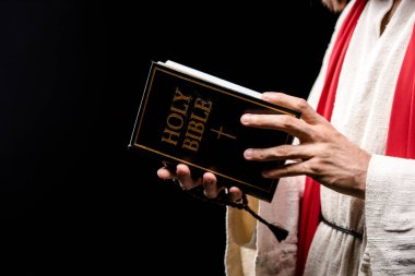 cropped view of man holding book with holy bible letters isolated on black
