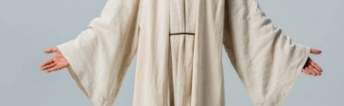 panoramic shot of man in jesus robe with outstretched hands isolated on grey