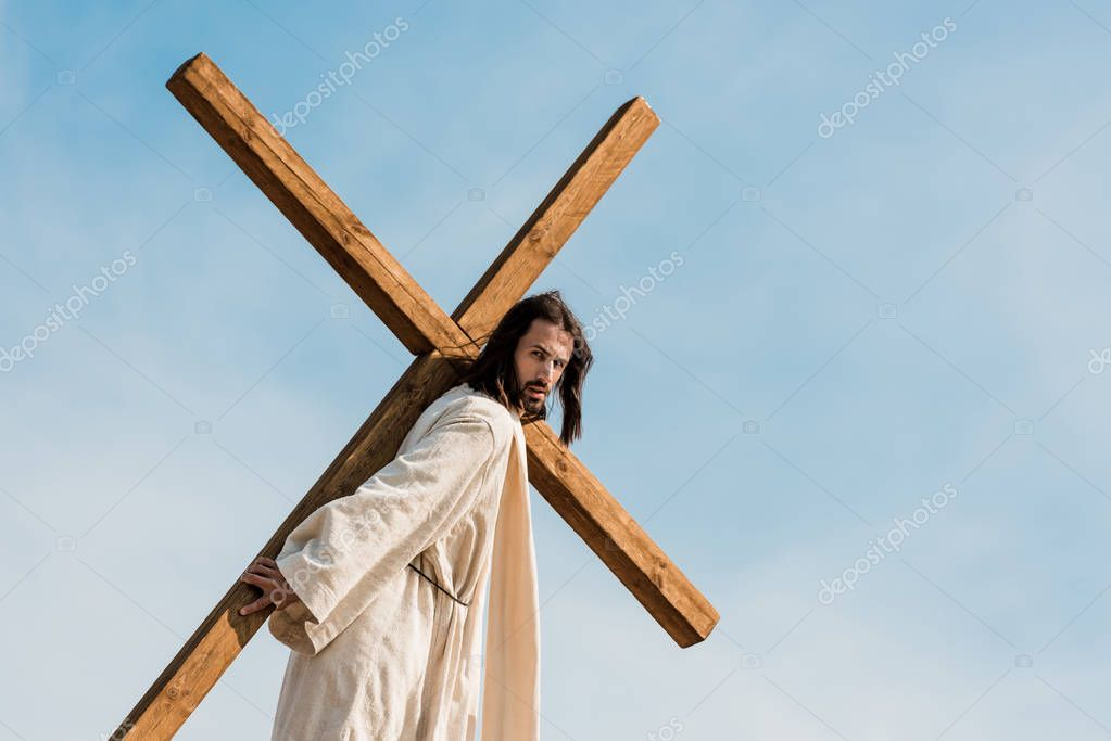 Bearded man walking with wooden cross against sky and clouds stock vector