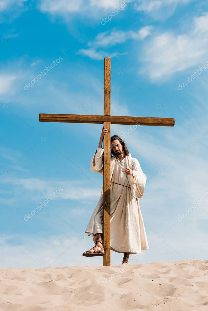 Bearded man standing with wooden cross in desert stock vector