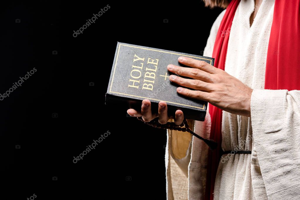 Cropped view of holding holy bible isolated on black stock vector