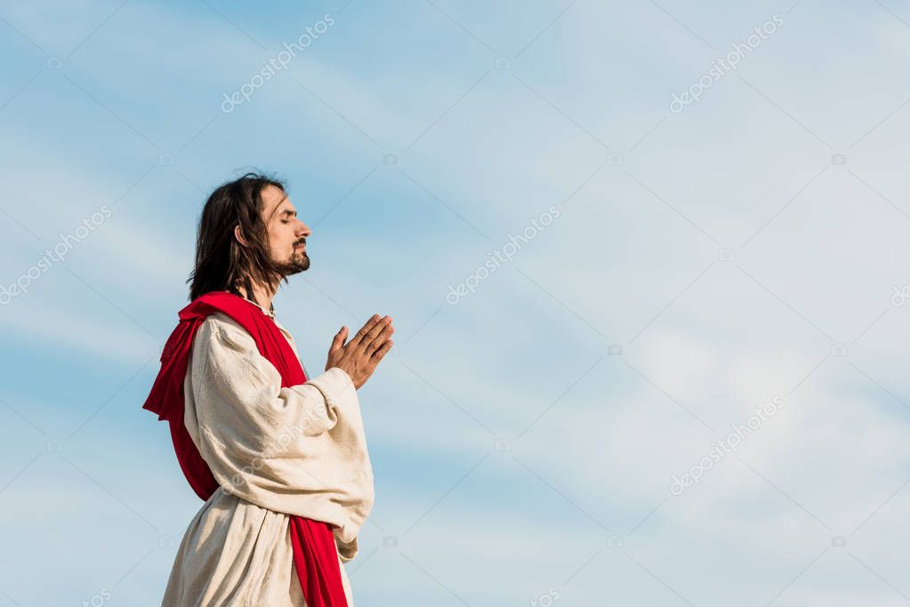 Man with closed eyes praying against blue sly stock vector