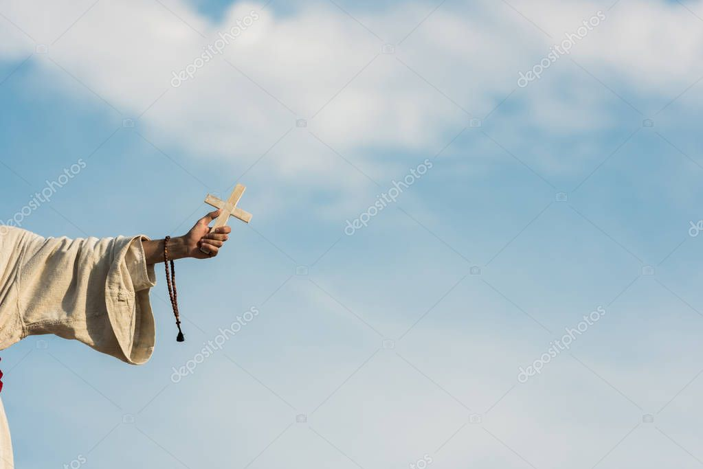 Cropped view of religious man holding cross and rosary beads against blue sky stock vector