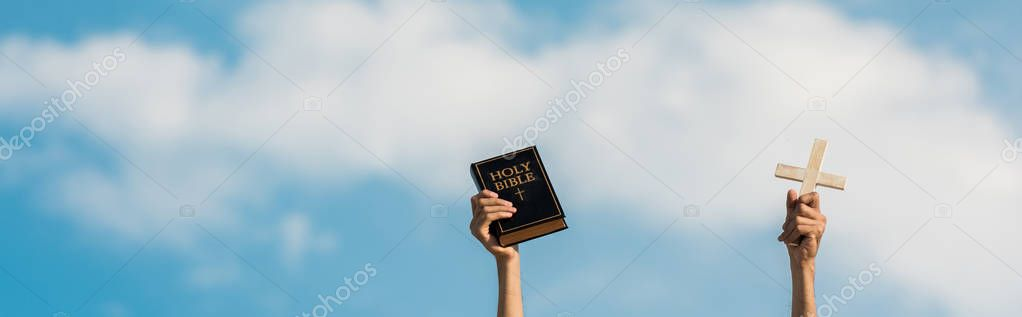Panoramic shot of man holding holy bible and cross against blue sky with clouds stock vector