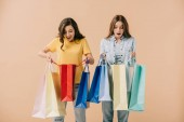 attractive and shocked friends holding shopping bags isolated on beige