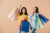 attractive and smiling friends holding shopping bags isolated on beige