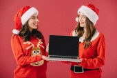 attractive and smiling women in sweaters and santa holding laptop isolated on red
