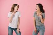Fotografie přitažlivé a usměvavé ženy v tričkách, které se na sebe dívají izolovaně na růžovém