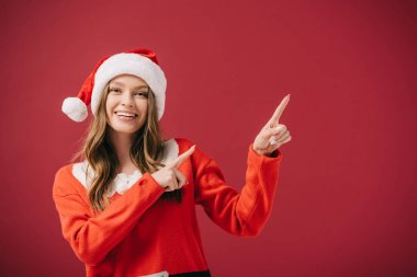 Attractive woman in santa hat and sweater pointing with fingers isolated on red stock vector