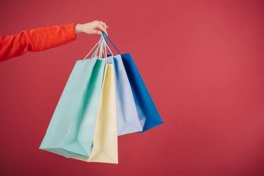 cropped view of woman holding shopping bags isolated on red