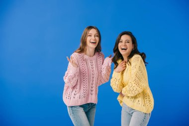 Attractive and smiling women in sweaters looking at camera isolated on blue stock vector
