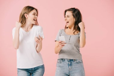 attractive and smiling women in t-shirts holding smartphones and showing yes gesture isolated on pink