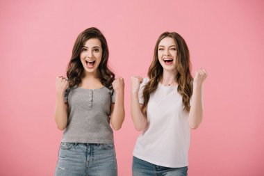 attractive and shocked women in t-shirts looking at camera and showing yes gestures isolated on pink