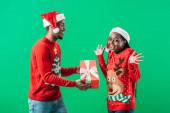 Afričan americký muž v červeném vánočním svetru a Santa Hat dává dárkové krabici překvapené ženě v zeleném