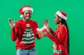 Africká Američanka v červeném vánočním svetru a Santa Hat dává dárkové krabici překvapenému člověku izolovanému na zeleném