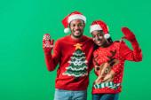 Afro-amerikai házaspár vörös karácsonyi pulóverek és Santa kalapok integetett kezet, és nézte a kamerát izolált zöld