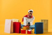 Photo African American man in winter outfit sitting and taking pictures of presents isolated on yellow