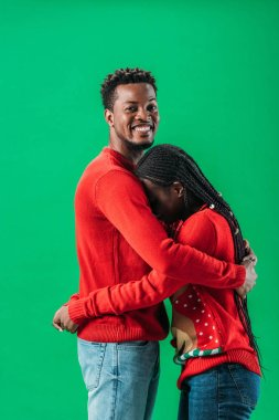 African American man hugging woman in red Christmas sweater isolated on green stock vector