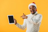 African American man in Santa hat pointing with finger at digital tablet with blank screen isolated on yellow