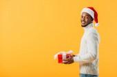 pohled ze strany afrického Američana v Santa Hatu přidržoval dárkové krabička a prohlížel si fotoaparát izolovaný na žlutém
