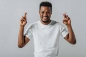 Afričan americký muž přidržoval prsty a díval se na kameru izolovanou na šedé