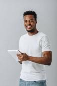 šťastný afroamerický muž, který drží digitální tabletu a dívá se na kameru izolovanou na šedé