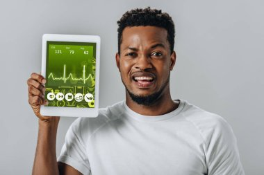 Upset African American man holding digital tablet with fitness application and looking at camera isolated on grey stock vector