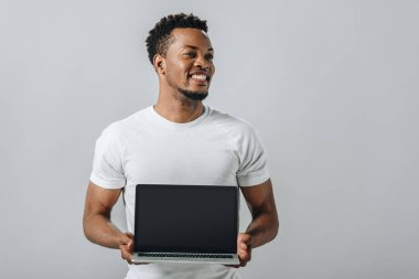 African American man smiling and showing laptop with blank screen and looking away isolated on grey stock vector