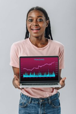 African American woman smiling and holding laptop with trading charts isolated on grey stock vector