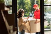 selektivní zaměření šťastný doručovací muž držící skříňku u ženy s perem