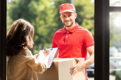 Photo happy delivery man holding box near woman with clipboard and pen
