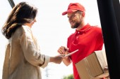 Photo cheerful delivery man looking at woman with digital tablet