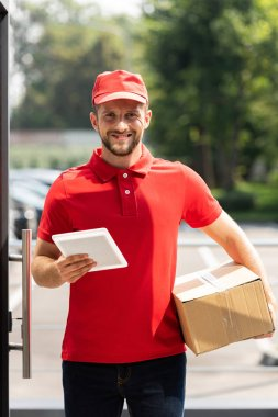 happy delivery man holding box and digital tablet
