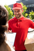 Photo selective focus of delivery man in cap holding box and looking at woman