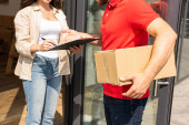 Photo cropped view of delivery man holding box near girl with clipboard