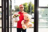 happy delivery man holding teddy bear and flowers