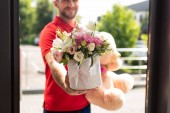 cropped view of bearded delivery man holding teddy bear and flowers