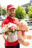 válogatós középpontjában a vidám átadás férfi Holding mackó és virágok