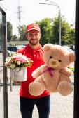 pozitivní dodávák, který drží medvídka a květiny