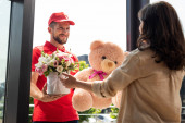 selective focus of cheerful delivery man holding teddy bear and flowers near woman