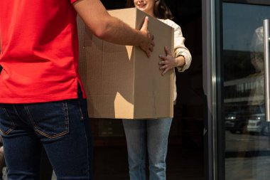 cropped view of delivery man giving carton box to girl