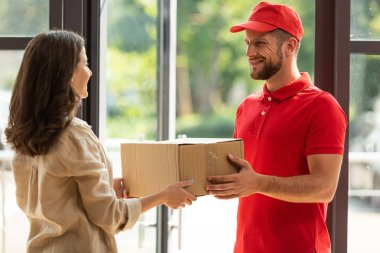 happy woman receiving carton box from delivery man