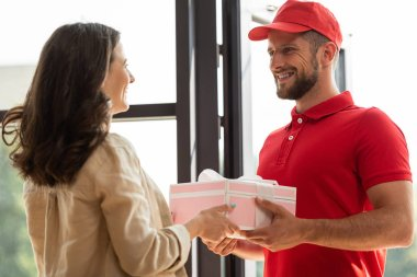 handsome delivery man in cap giving pink present to happy woman