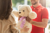 cropped view of happy bearded man giving teddy bear to woman